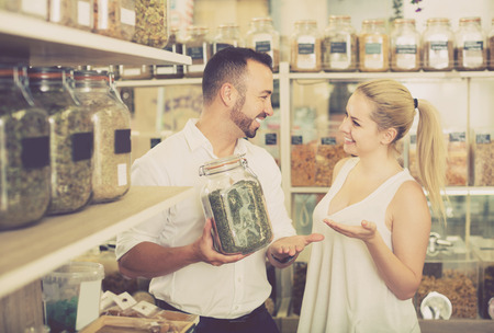 a jar stand: Happy woman and man holding glass can with dried herbs in organic shop Stock Photo