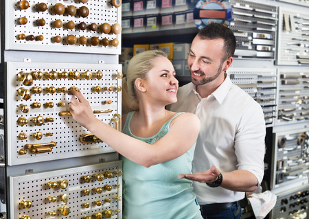 lintel: Young cheerful couple standing next to a showcase with door handles and choosing one. Focus on both persons