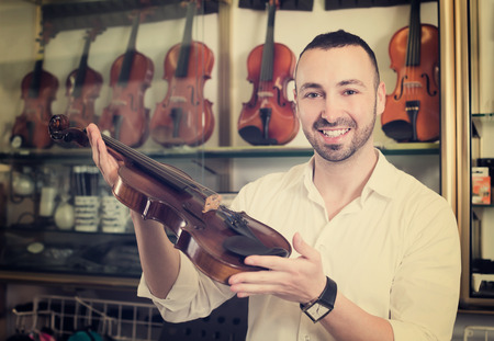 selecting: Happy male musician selecting classical violin in music instruments studio