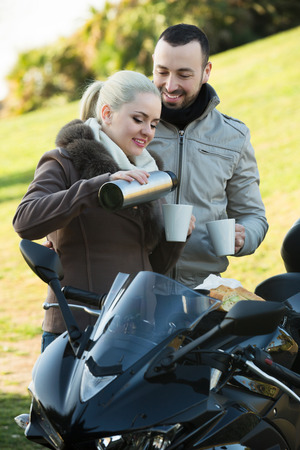 sandwitch: Young positive couple drinking coffee and chatting near motorcycle Stock Photo