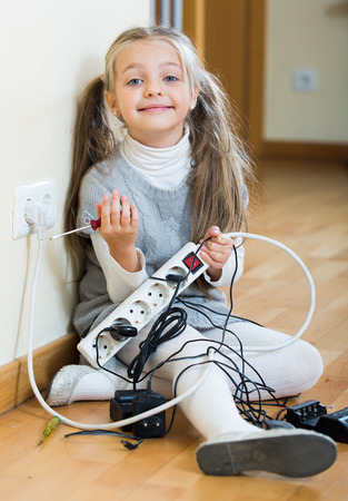 perilous: Small girl wearing ponytails playing with electricity and smiling