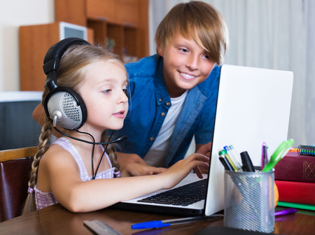 Happy teenager and his sister surfing internet indoors and smiling Stock Photo