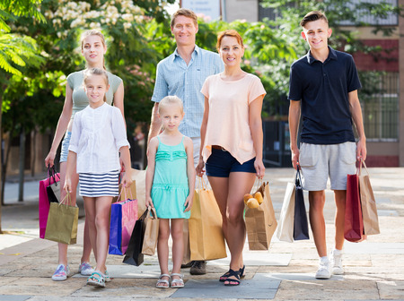 gladly: Smiling adult parents with four kids gladly shopping in town
