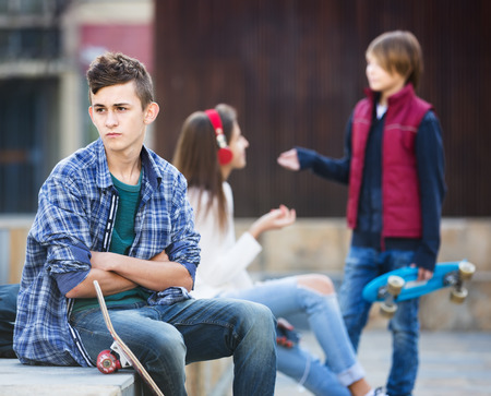sullen: Upset male teen sitting aside of girlfriend talking with boy in the city