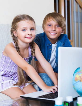 Teenager and his sister surfing internet indoors and smiling Stock Photo