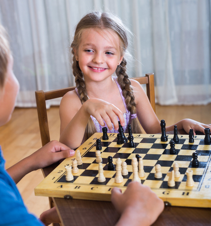 Portrait of happy children at chess board indoors