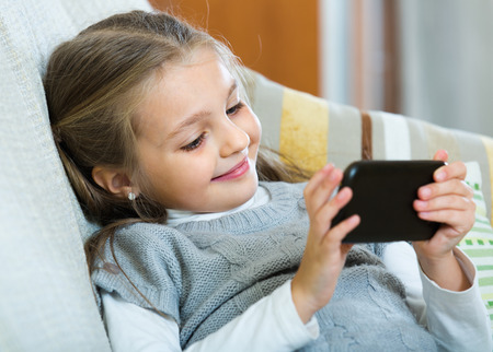 Smiling little girl playing games on smartphone at home