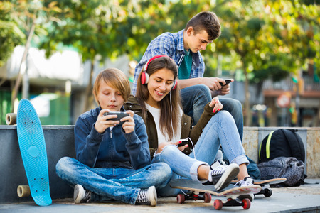 teens playing: Active cheerful teens playing on smarthphones and listening to music