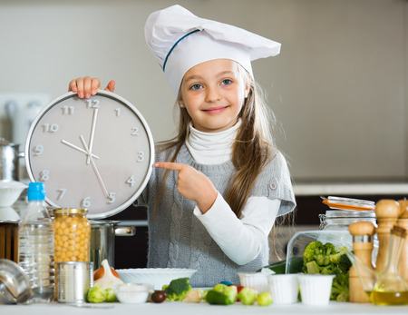 ponytails: Girl with ponytails holding clock at kitchen table and smiling Stock Photo