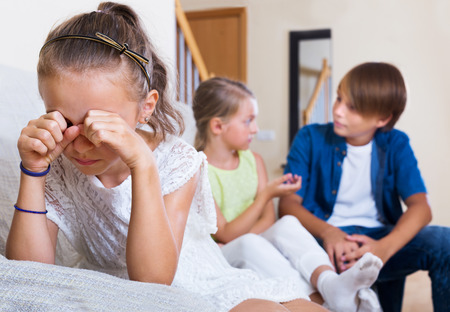 banter: Envy child sitting aside of american boy and girl at home Stock Photo