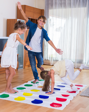 twister: Group of happy children playing at twister indoors