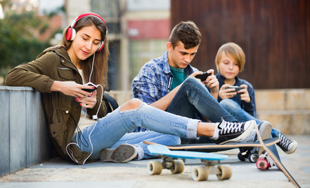 teens playing: Happy smiling teens playing on smarthphones and listening to music Stock Photo