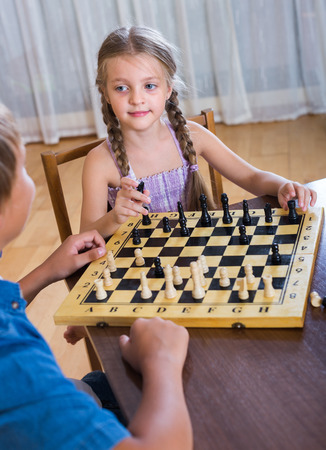 Brother teaching his little sister playing chess at home