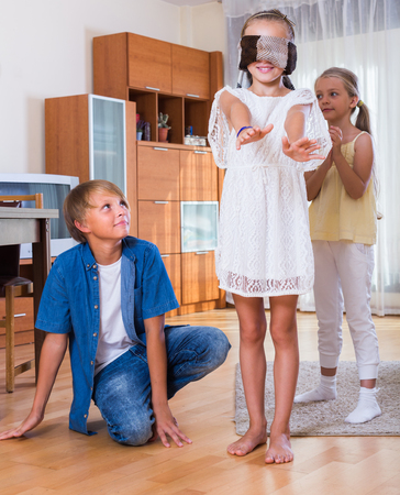 romp: Happy children playing with blindfold in the living room