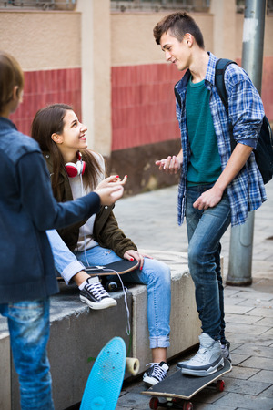 blabbing: Portrait of teenage males and girl chatting in autumn day