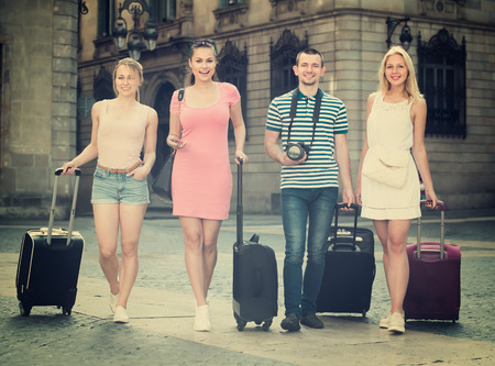 clique: Four positive traveling persons walking together with luggage and looking around in city Stock Photo
