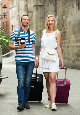 dragging: portrait of happy man and woman taking walk and dragging luggage bags in town on summer day