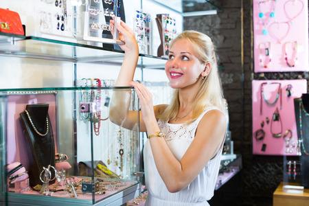 personal shopper: joyful  blonde girl purchasing fashion earrings in bijouterie boutique Stock Photo