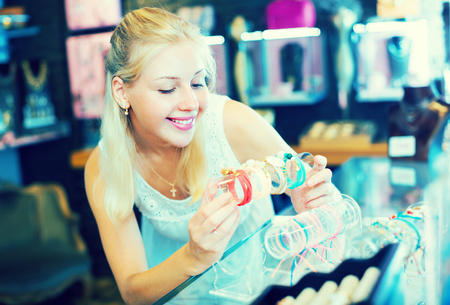 excited smiling girl customer  selecting new bracelet in bijouterie shop Stock Photo