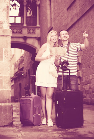hollidays: Man and woman on hollidays walking in city centre and takeing suitcases with you Stock Photo
