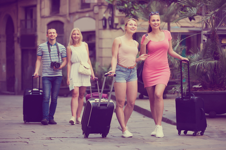 clique: Two adult traveling girls walking together with luggage and looking around in city