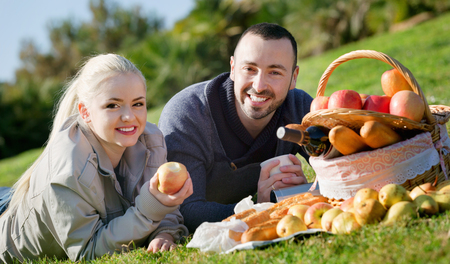 sandwitch: Young smiling couple chatting as having picnic in sunny day