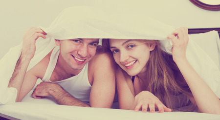 nearness: Young loving couple lounging in bed hiding under cover in bedroom