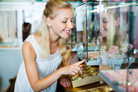 personal shopper: Portrait of young cheerful woman standing next to glass showcases in shop with bijouterie