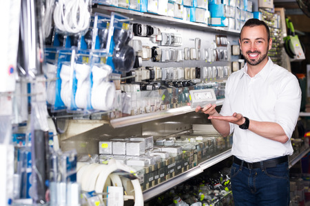 selecting: Happy young man selecting electric socket in household department Stock Photo