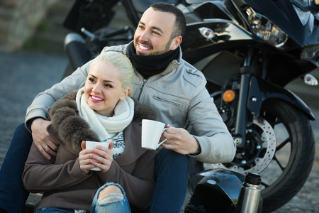 25s: Portrait of young adults drinking coffee and chatting near motorcycle in spring
