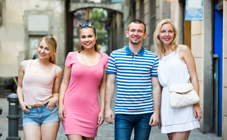clique: portrait of four happy young people taking walk in town together on summer day Stock Photo