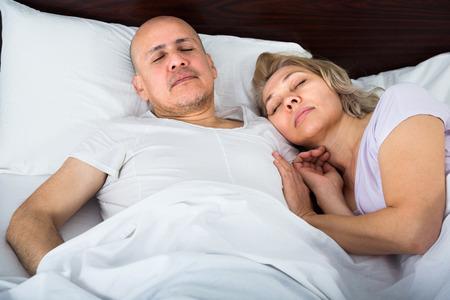 tight focus: Loving senior family couple sleeping tight in bed at night. Focus on man