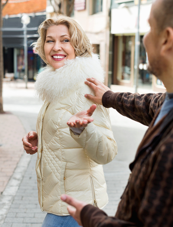 sidewalk talk: Senior man flirting with smiling blonde woman outdoors