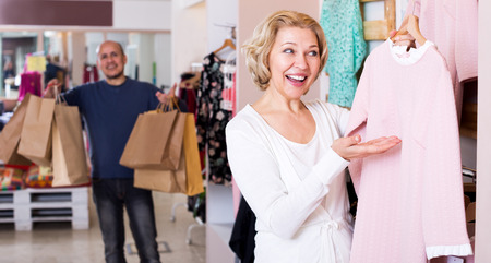 indignant: Smiling man with bags waiting for mature woman selecting dress in boutique