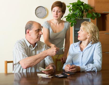 money in the pocket: hija adulta en la ley pidiendo a los padres maduros de dinero de bolsillo