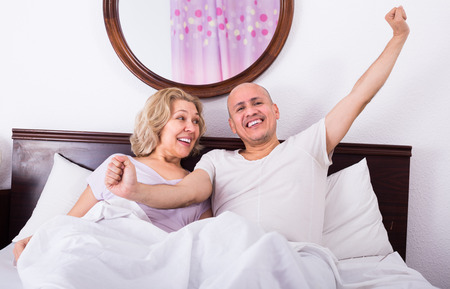 romantic mature adults lying in family bed and smiling Stock Photo