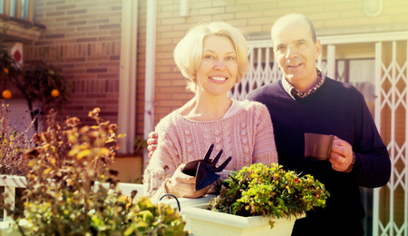 Elderly woman talking with male neighbor at balcon Stock Photo