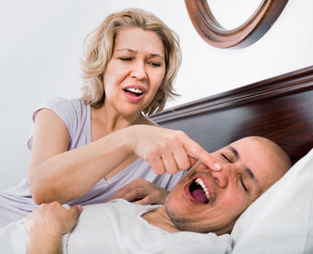 Mature exhausted tired girl looking at snoring boyfriend sleeping tight