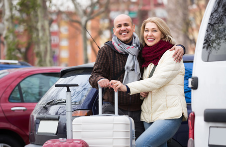 a two wheeled vehicle: Cheerful mature couple with luggage standing at street and smiling. Focus on man Stock Photo