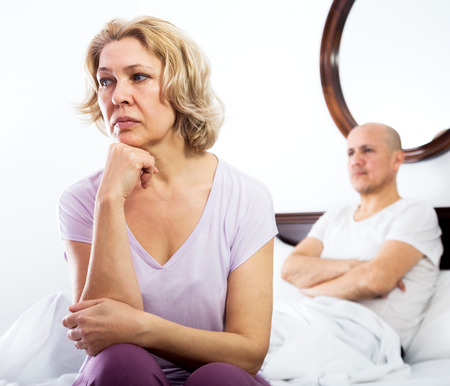 scandals: Mature man and unhappy woman getting through scandals and blamings in bedroom