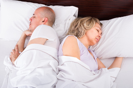 Mature family couple sleeping tight in bed at night Stock Photo