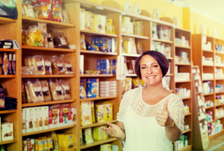 dietary supplements: ?Smiling mature woman customer shopping dietary supplements in healthy food store