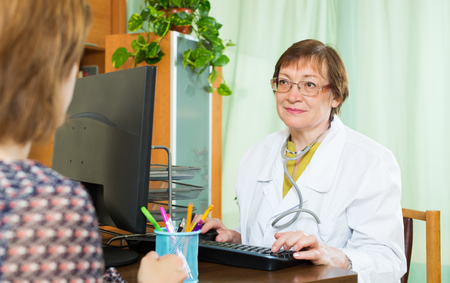 Elderly woman doctor communicates with patient sitting at PC