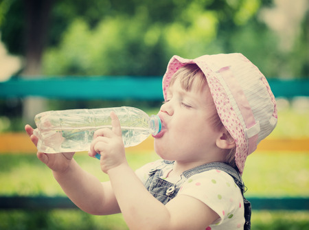 2 years: 2 years child drinks from plastic bottle in park