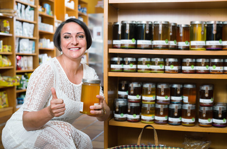 mature brunette: Positive smiling mature brunette woman choosing honey from assortment in drugstore Stock Photo