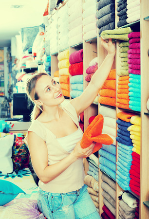 consuming: Cheerful smiling woman buying  soft towels in home textile store