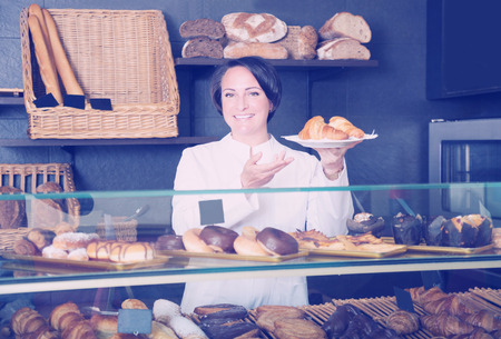 suggesting: Smiling adult cook gladly suggesting pastry in the cafeteria Stock Photo
