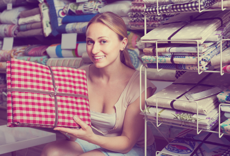 spanish home: portrait of happy spanish female customer choosing tablecloths in home textile section in shop Stock Photo