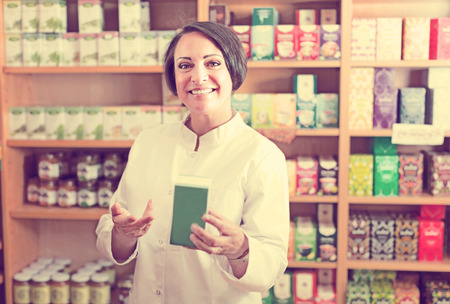 nutrientes: Feliz vendedor hembra madura celebración de nutrientes de la dieta en la tienda farmacéutica Foto de archivo