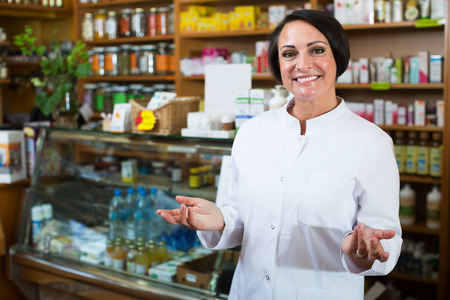 biologically: Portrait of positive mature pharmacist woman in biologically active dietary supplements store